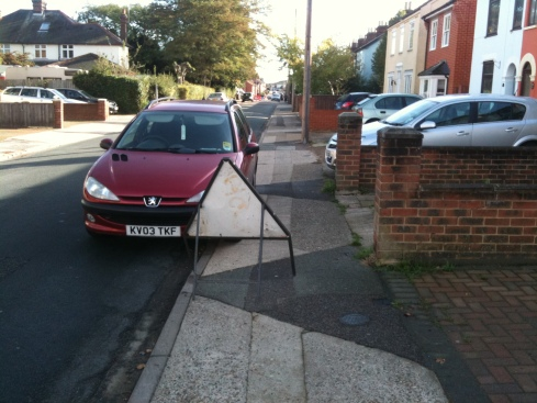 Blocking the pavement illegally and useless due to parked car!